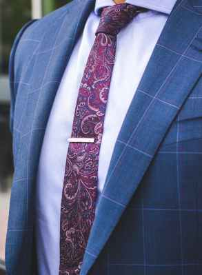 person in blue suit and red paisley necktie