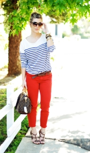A woman wearing a striped shirt, sunglasses, and red pants. Image from Wikimedia Commons.